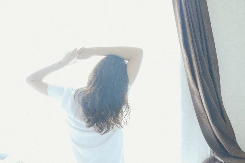 朝、窓に向かう女性