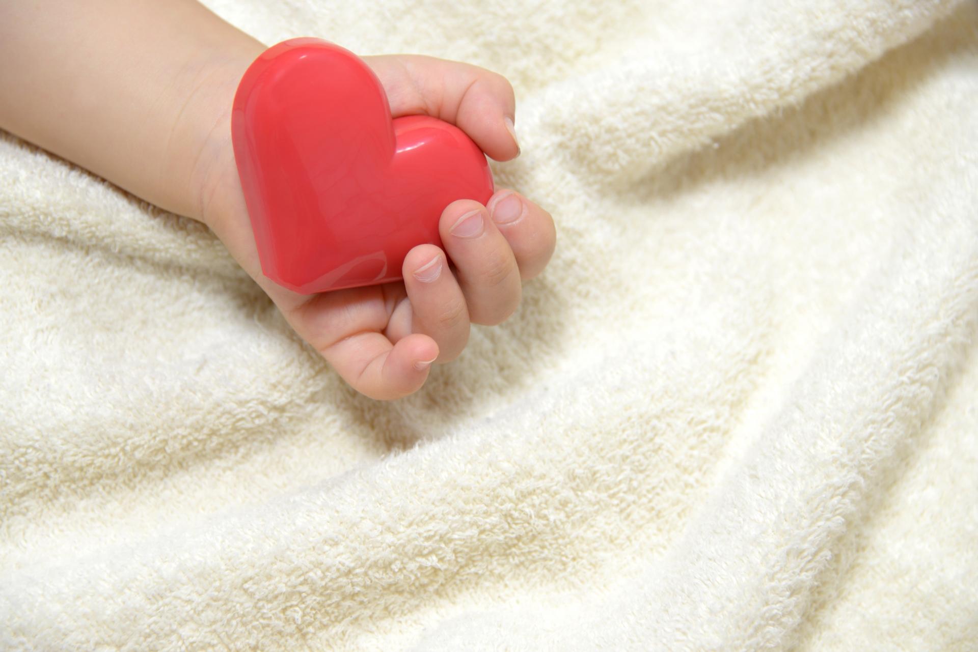 ハートのおもちゃを持つ赤ちゃん