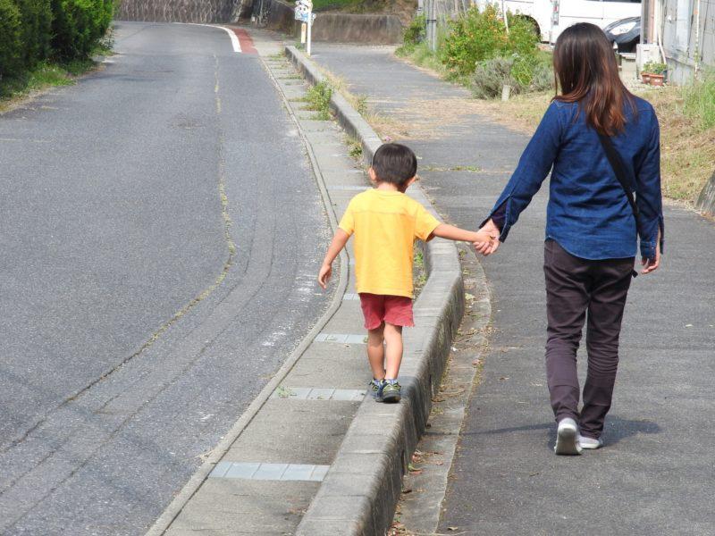 道路止めを歩く子どもと母親
