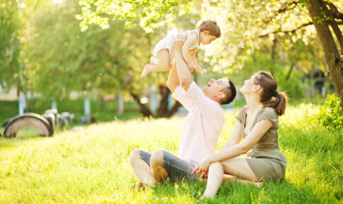 赤ちゃんを抱き上げる男性と見守る女性